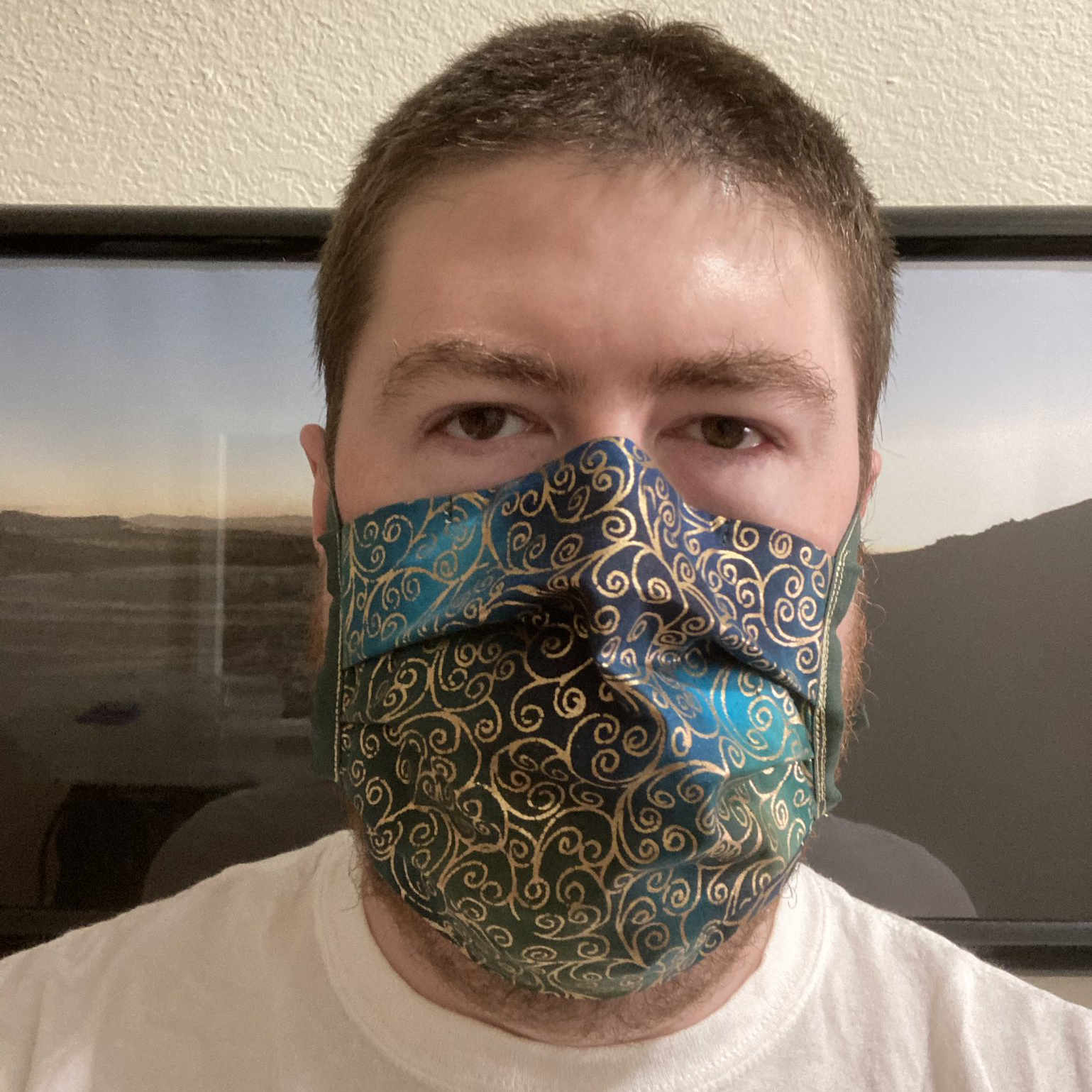 Me wearing a mask with a gold-colored scrolls pattern printed on a blue-and-green batik fabric.