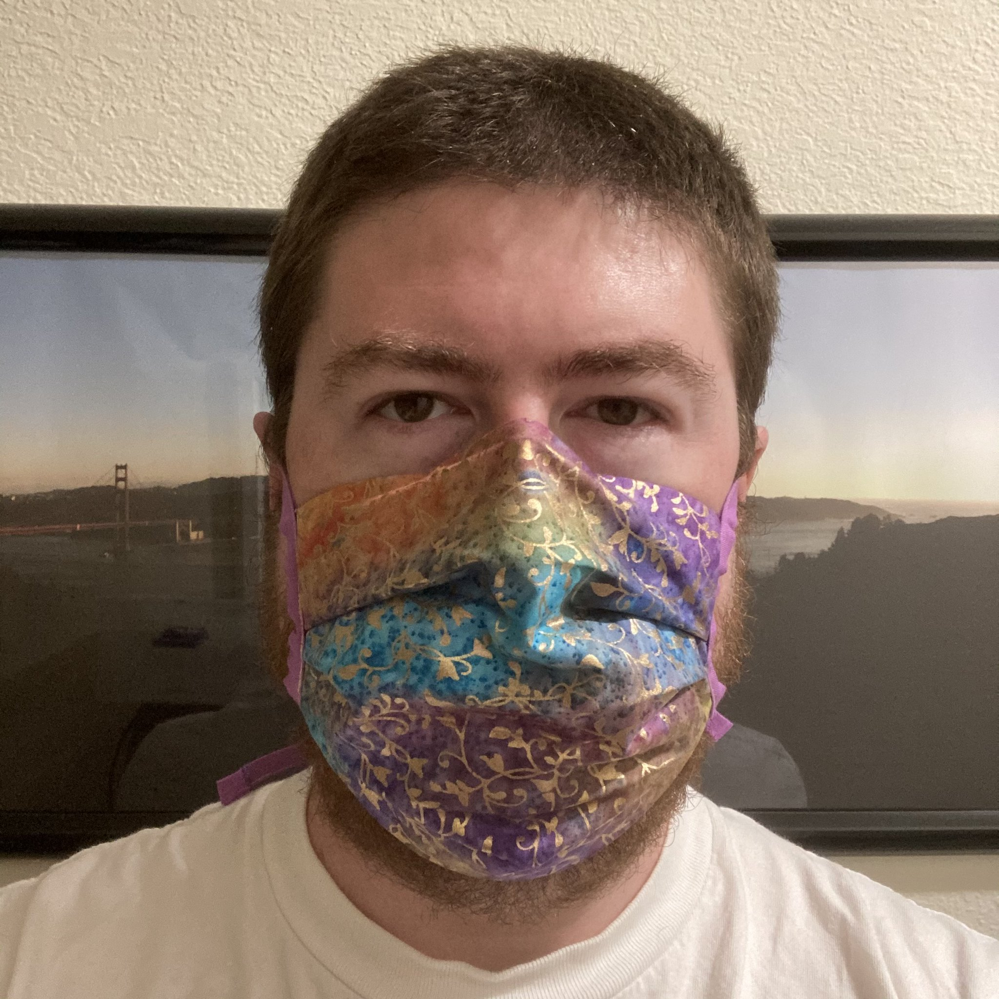 Me wearing a mask with a gold-colored ivy pattern printed on a many-colored batik fabric.