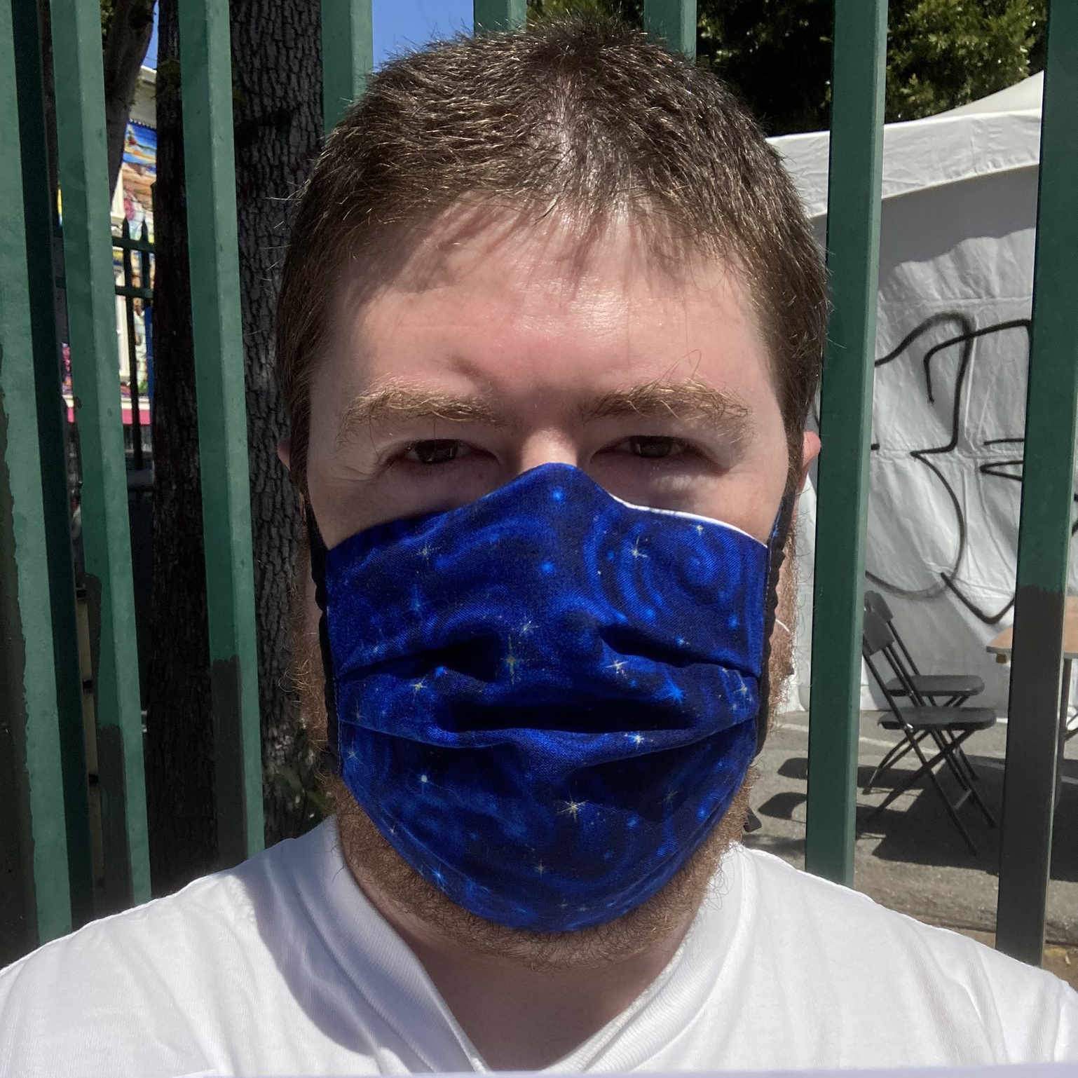 Me wearing a mask with stars printed on a blue outer-space pattern fabric.